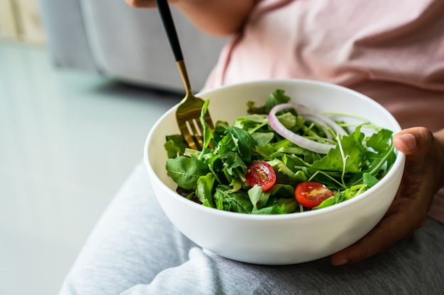 Eat green concept, young women eatting organic fresh vegetable salad in ceramic bowl at home.