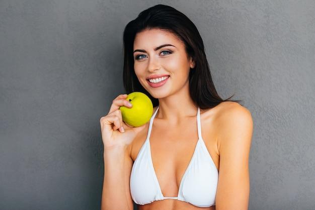 健康的に食べる!青リンゴを保持し、灰色の背景に立って笑っている白いビキニの魅力的な若い女性