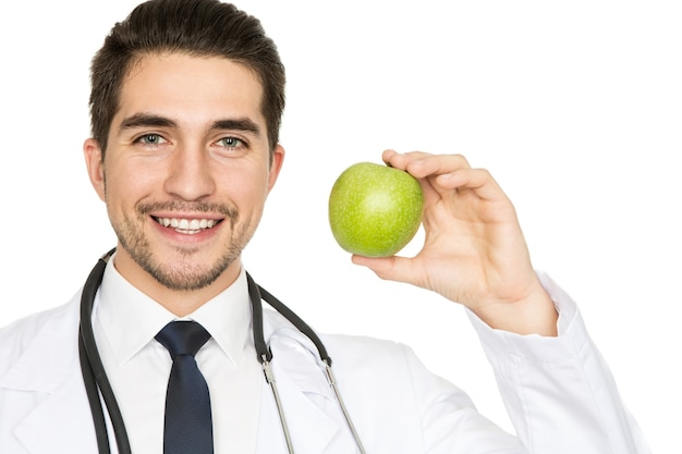 Eat healthy. closeup portrait of a handsome doctor smiling widely holding an apple