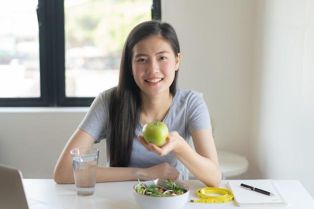 Ешьте здоровую пищу на велнес-образе жизни. молодая женщина красоты держа зеленое яблоко в ее руке и имея салат.