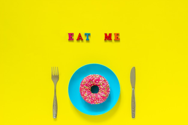 Eat me pink donut on blue plate and cutlery knife fork on yellow background.