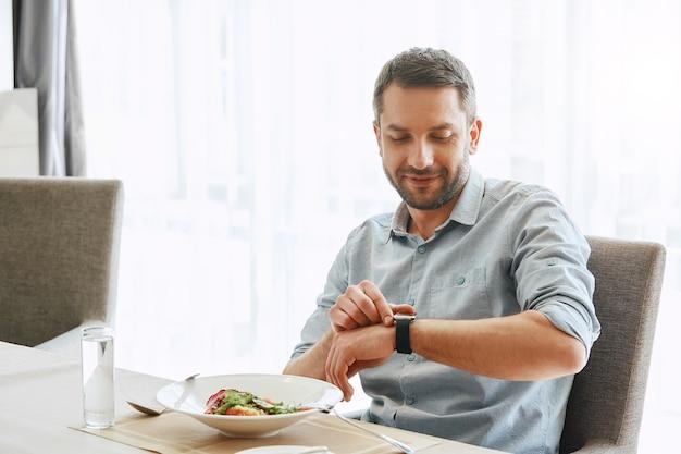 샐러드를 먹는 옳고 가벼운 미소 잘 생긴 사업가 먹기