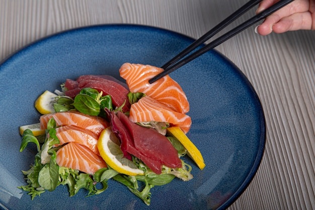 Eat sashimi in the japanese restaurant, with closed chopsticks. raw fish.