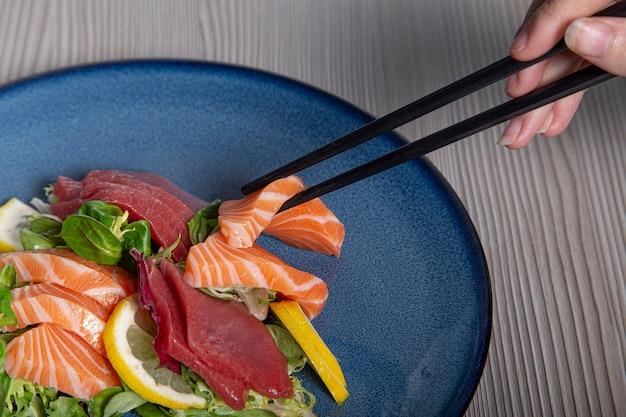 Eat sashimi with closed chopsticks. raw fish. isolated