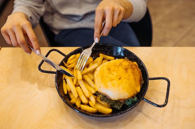 나이프와 포크로 먹어 감자 튀김과 함께 식욕을 돋우는 고기 버거