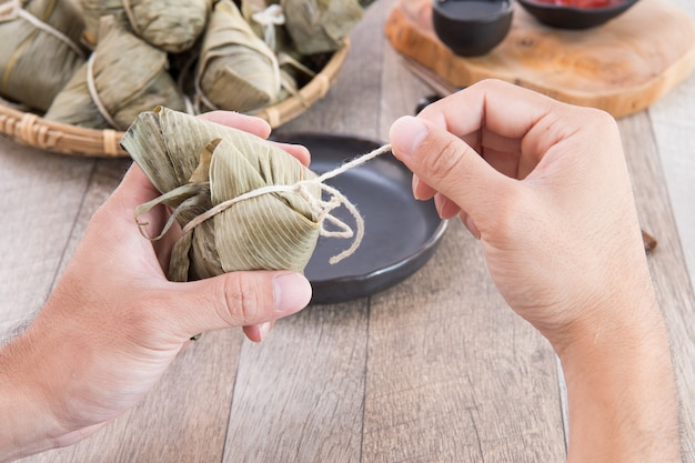 아시아 전통 음식 인 용선 축제에서 종즈 (쌀 만두) 먹기