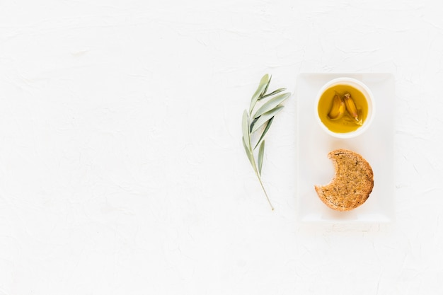 Eaten bread with garlic clove in the oil bowl on white background