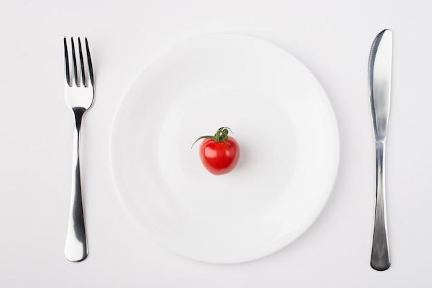 저칼로리 다이어트 개념을 먹고 있습니다. 흰색 배경에 따로 분리된 포크와 나이프가 있는 단일 토마토가 있는 접시의 머리 위 평면 사진