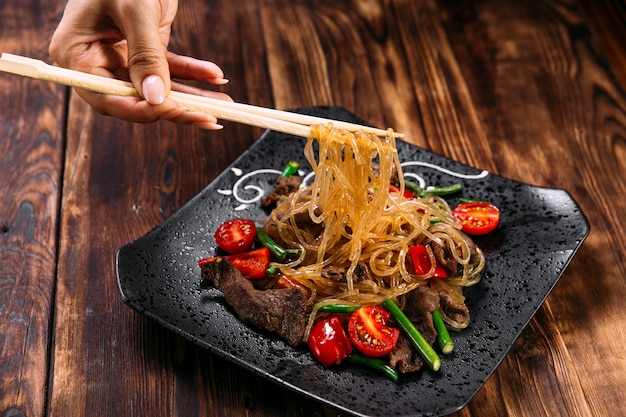 Еда аппетитного азиатского блюда с лапшой фунчоза