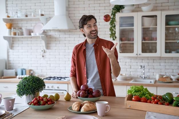 毎朝リンゴを食べるカジュアルな服を着た若い幸せなひげを生やした男が赤いリンゴを投げて