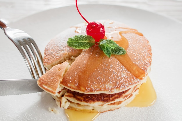 レストランで食べる。甘いアメリカンパンケーキ。白いプレートの背景にチェリーと蜂蜜のクレープ。伝統的なアメリカ料理。