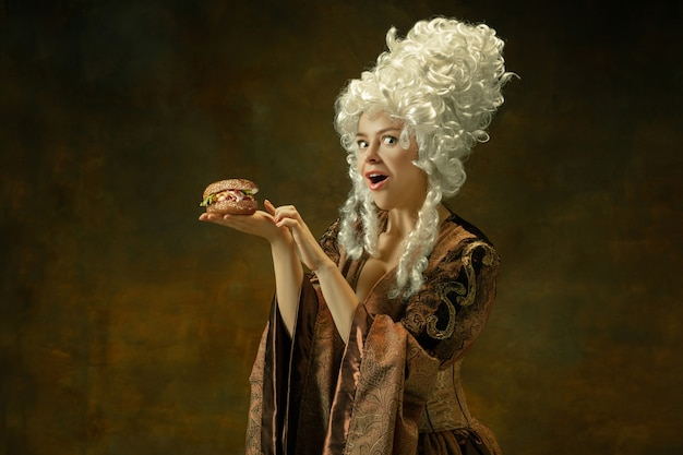 Eating burger wondered. portrait of medieval young woman in brown vintage clothing on dark background. female model as a duchess, royal person. concept of comparison of eras, modern, fashion, beauty.