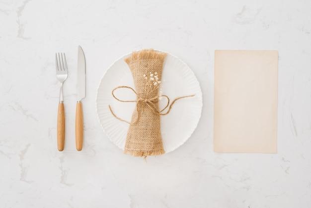 食べるコンセプト。白い石の背景にスプーン、フォーク、白い皿。