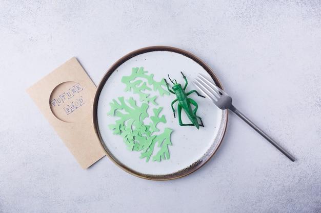 귀뚜라미 곤충과 해초를 접시에 담아 음식으로 먹기 위해 식용 곤충을 먹으면 미래의 음식 개념을 위해 먹을 수 있는 고단백 식사의 좋은 공급원입니다. 고품질 사진