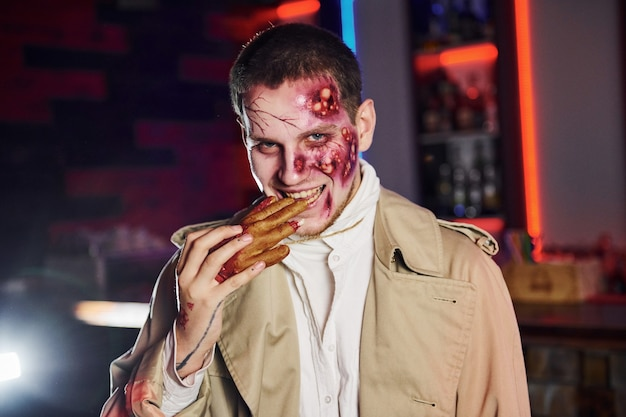 Eating dead hand. portrait of man that is on the thematic halloween party in zombie makeup and costume.