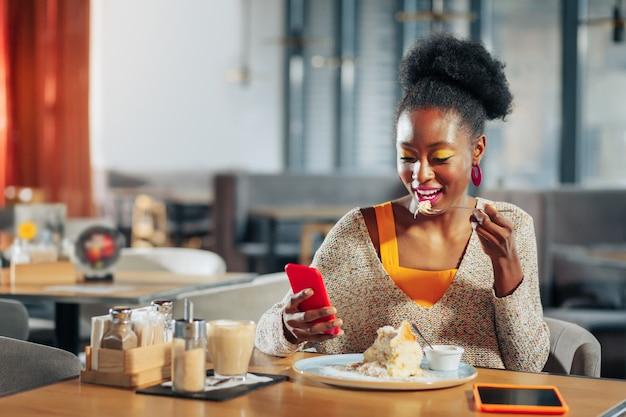 デザートを食べる明るい化粧をした女性がおいしいデザートを食べ、電話でメッセージを読む