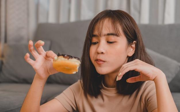 테이크아웃 및 배달 시 도넛을 먹습니다. 집으로 돌아가는 패스트푸드 테이크아웃. 거실에서 아시아 여성의 라이프 스타일입니다. 사회적 거리두기와 뉴노멀.