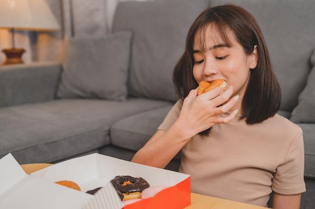 테이크아웃 및 배달 시 도넛을 먹습니다. 집으로 돌아가는 패스트 푸드 테이크 아웃. 거실에서 아시아 여성의 라이프 스타일입니다. 사회적 거리두기와 뉴노멀.