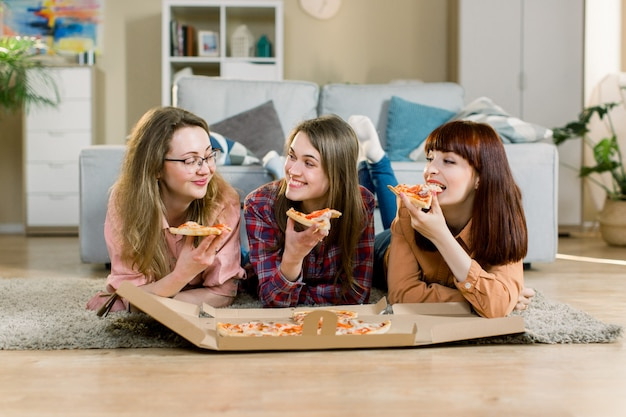 Eating fast food. happy three beautiful friends laughing, eating pizza at home party. women having dinner together, enjoying meal. leisure, friendship, celebration and people concept