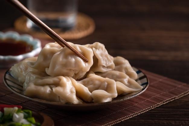 醤油と木製のテーブルの背景に新鮮でおいしいゆで餃子、餃子を食べる