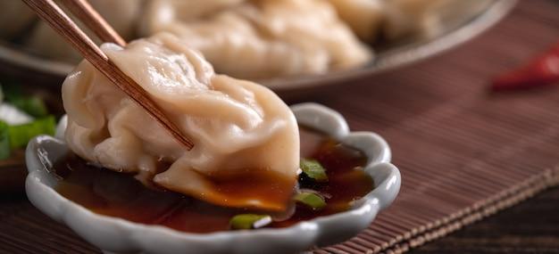 醤油で木のテーブルの表面に新鮮でおいしいゆで餃子、餃子を食べる