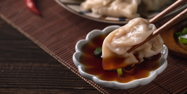 Eating fresh, delicious boiled dumplings, jiaozi on wooden table background with soy sauce