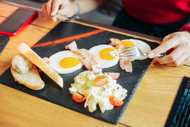 Eating fried eggs. top view of woman eating delicious fried eggs with bacon and salad
