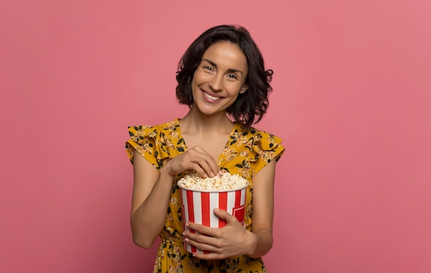 Eating habits. cheerful young lady, who is looking in the camera with a big smile, while eating popcorn.
