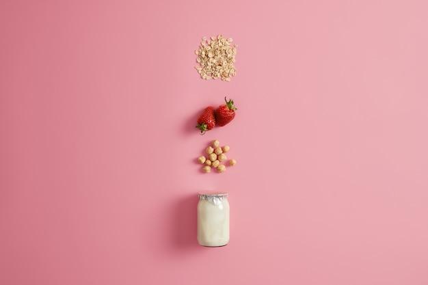健康的な朝食を食べる、きれいな食事、ダイエット、デトックス食品、菜食主義の概念。オートミールを作るためのヘーゼルナッツ、熟したイチゴ、オート麦のヨーグルト。自家製お粥の材料。上面図