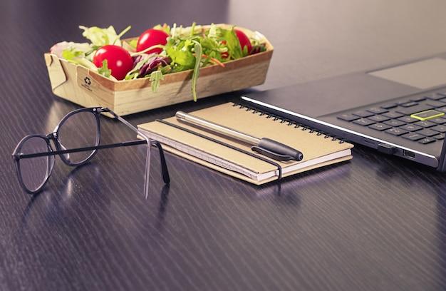 Еда здорового бизнес-ланча на рабочем месте зеленый салат перерабатываемый ланч бокс ноутбук ручка для ноутбука