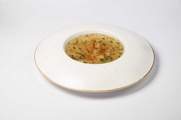 Eating healthy chicken broth with vegetables and herbs on white surface.