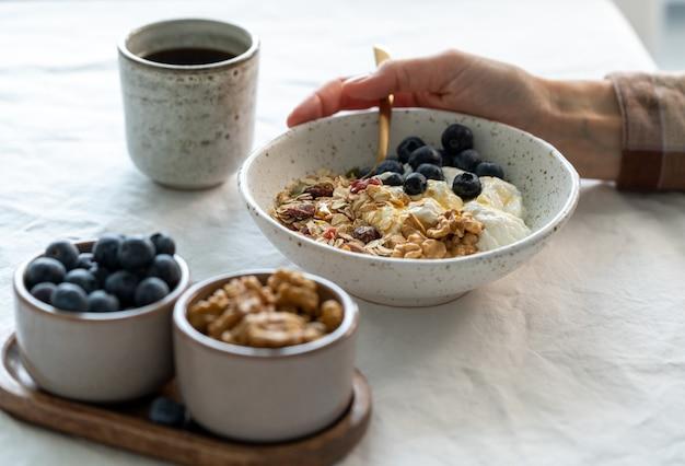 Есть завтрак здорового образа жизни с мюсли мюсли и йогурт в шаре на белом столе, зерновые хлопья с семенами орехов. органические утренние диетические блюда с овсяными хлопьями для здоровья.