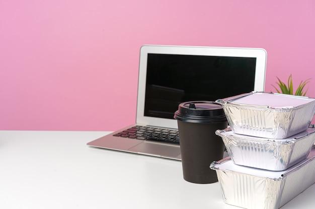 オフィスで食べる。ホームオフィス。食品配達パッケージと作業テーブル上のオープンラップトップ