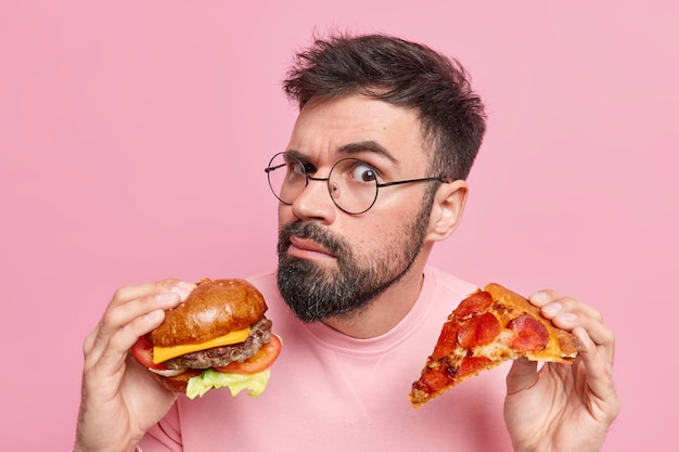 Eating junk food. serious attentive bearded adult european man holds tasty hamburger and slice of pizza wears spectacles eats cheat meal