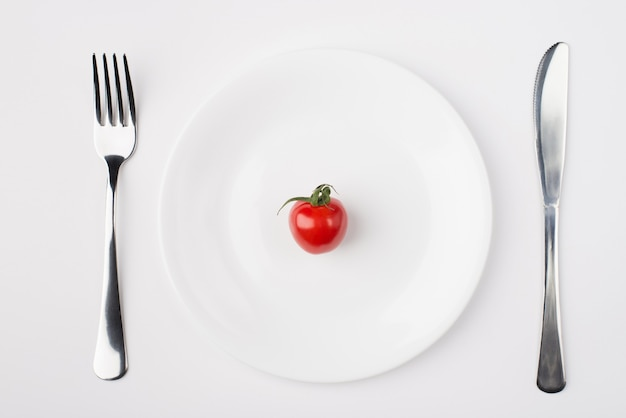 Eating a low calorie diet concept. top above overhead flat-lay view photo of a plate with a single tomato with fork and knife aside isolated on white background