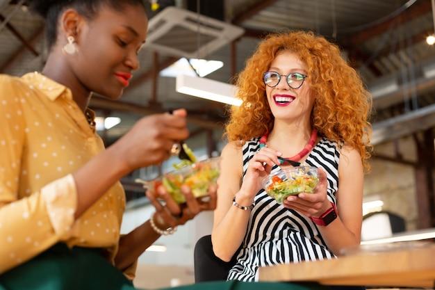 Обедаем вместе. красивые модные офисные работники вместе обедают в офисе