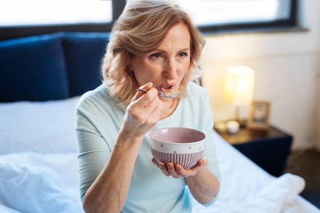 Употребление утренней каши. коротко стриженная зрелая дама несет металлическую ложку и пробует завтрак, сидя на кровати