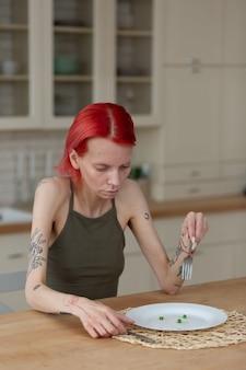 Ничего не ест. рыжая худая молодая женщина страдает анорексией, ничего не ест