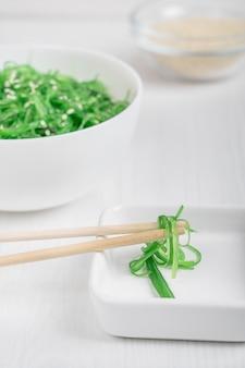 Салат из водорослей чука вакаме с семенами кунжута, поданный в белом блюдце с бамбуковыми палочками для еды