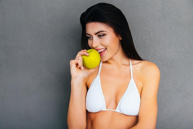 健康的な食べ物だけを食べる。青リンゴを食べて、灰色の背景に立って笑っている白いビキニの魅力的な若い女性