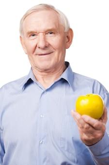 健康的な食べ物だけを食べる。白い背景に立っている間、ハートの小道具を保持しているシャツを着た年配の男性の笑顔