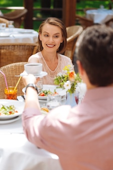 Питание вне дома. пара счастливых красивых личностей, которые чувствуют себя невероятно потрясающе и расслабленно во время еды вместе
