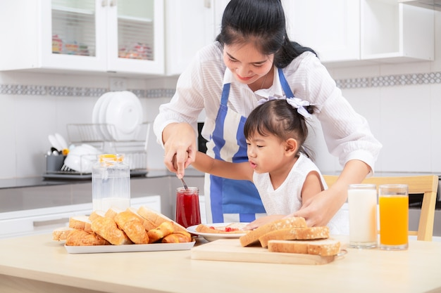 Eating and people concept - asian happy mother and daughter having breakfast at home.