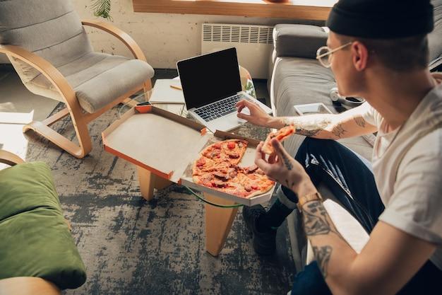 ピザを食べる。オンラインコース、スマートスクール中に自宅で勉強している男性。隔離された状態でクラスや職業を取得し、コロナウイルスの拡散を隔離します。ノートパソコン、スマートフォン、ヘッドホンを使用。