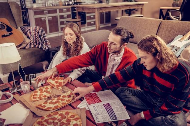 ピザを食べる。音楽を作曲した後にピザを食べる音楽バンドの3人の創造的な参加者