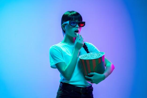 네온에서 그라데이션 블루퍼플 스튜디오 배경에 팝콘을 먹는 젊은 아시아 여성 초상화