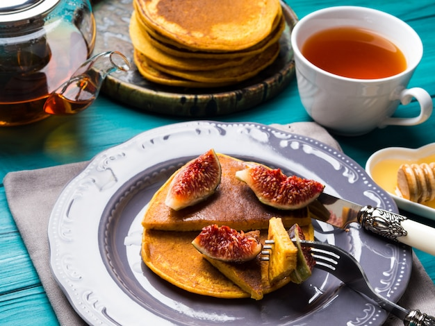 Eating pumpkin pancakes with figs and honey