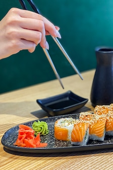 Eating roll sushi in japanese restaurant, hand with chopsticks