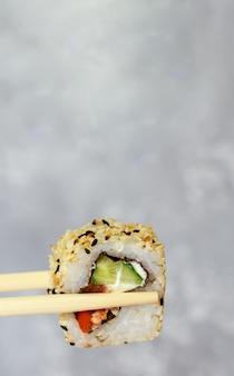 箸で寿司を食べるクローズアップ。レストランで日本食の巻き寿司。
