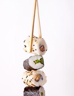 箸で寿司を食べる。白い背景で隔離のレストランで寿司ロール日本食。